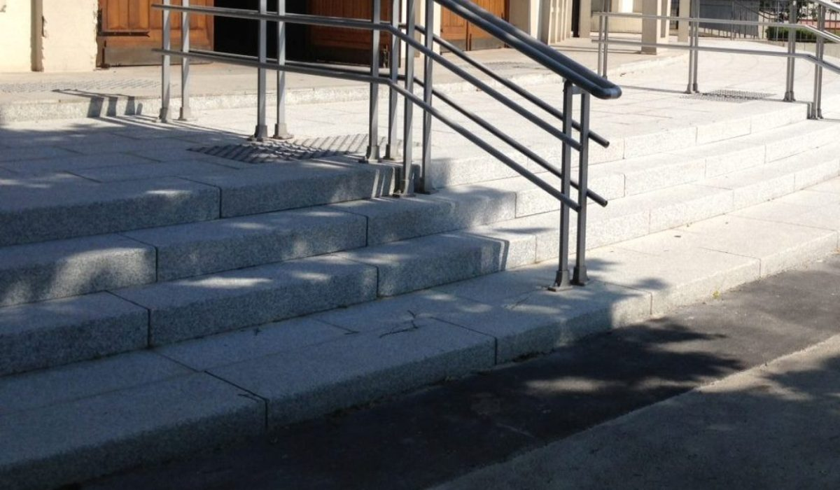 Solid curved steps in grey Pascual granite and tactile blister paving in black Santiago granite.